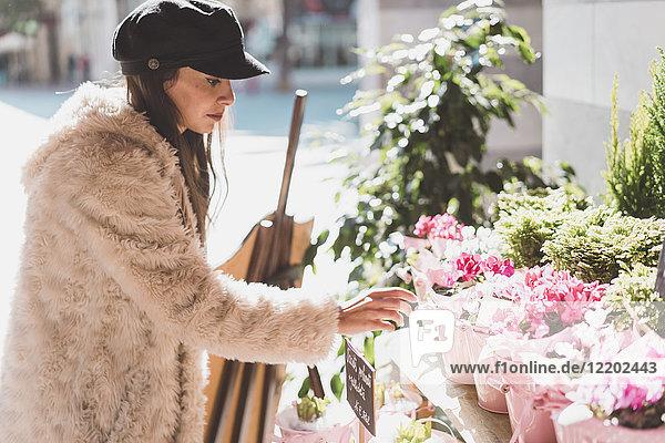 Stilvolle junge Frau beim Blumenkauf in der Stadt