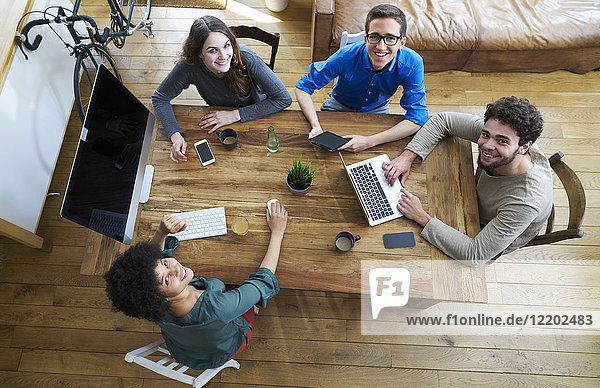 Elevated view of smiling coworkers working together at wooden table in office