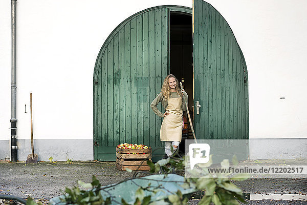 Smiling woman on a farm standing at crate with apples