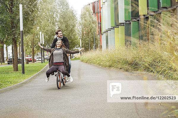 Ein glückliches Paar auf einem Fahrrad auf einem Weg