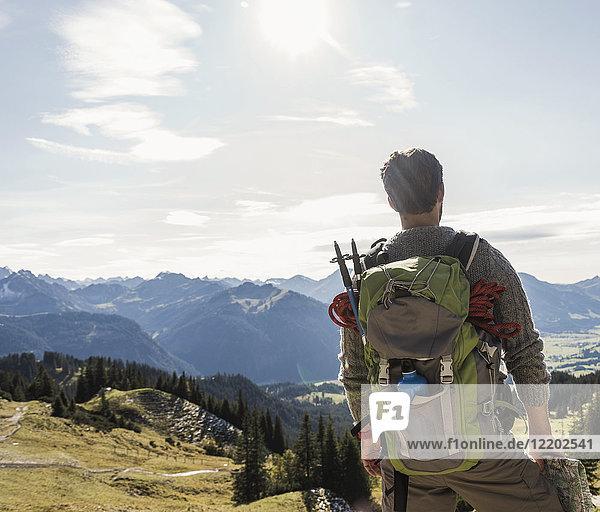 Österreich  Tirol  junger Mann in der Bergwelt mit Blick auf die Aussicht
