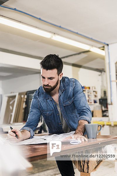 Mann beim Betrachten des Entwurfs in der Werkstatt