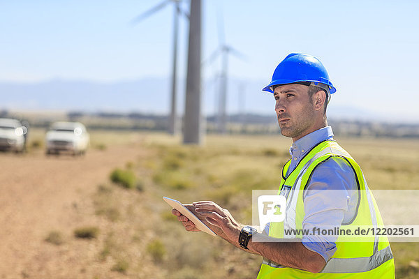 Engineer using tablet on a wind farm