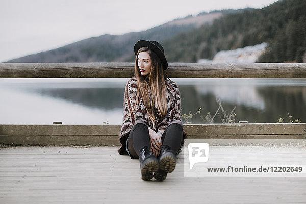 Porträt der modischen jungen Frau mit Hut und Poncho auf Holzbrücke sitzend