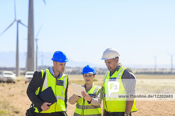 Three engineers with tablet discussing on a wind farm