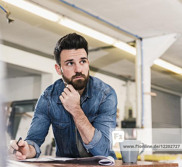 Mann schaut vom Entwurf in der Werkstatt auf
