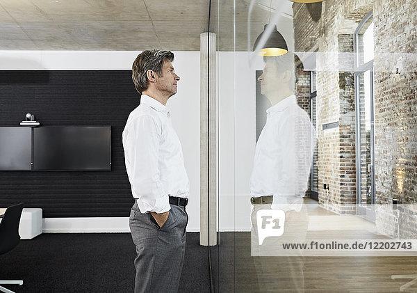 Der reife Geschäftsmann spiegelt sich in der Glasscheibe des modernen Konferenzraumes.