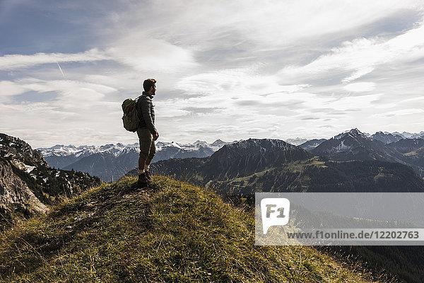 Österreich  Tirol  junger Mann steht in der Berglandschaft und schaut auf die Aussicht