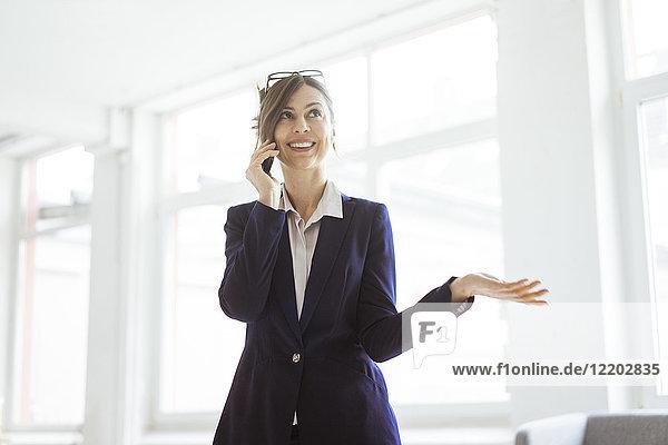 Lächelnde Geschäftsfrau am Handy im hellen Zimmer