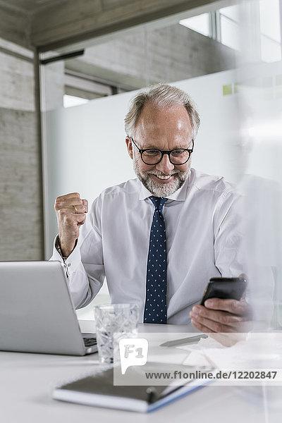 Glücklicher reifer Geschäftsmann am Schreibtisch im Büro mit Blick auf das Handy