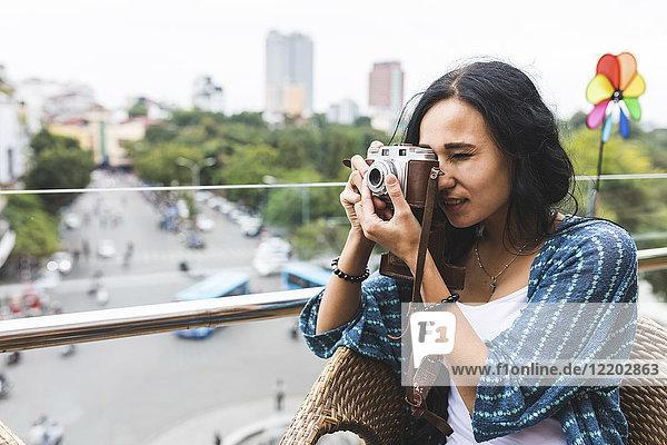 Vietnam,  Hanoi,  junge Frau beim Fotografieren mit altmodischer Kamera