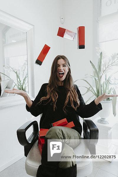 Aufgeregte junge Frau jongliert mit Kosmetik im Schönheitssalon