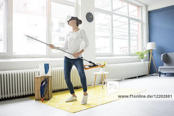 Vital Frau zu Hause mit VR-Brille  die den Boden wischt.