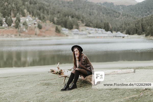 Fashionable young woman wearing hat and poncho sitting on log on a meadow