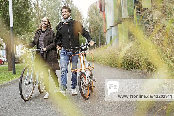 Lächelndes Paar  das mit Fahrrädern auf einer Straße spazieren geht