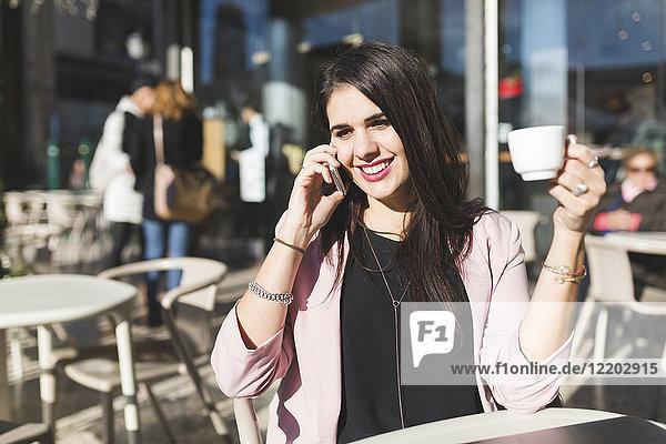Lächelnde junge Geschäftsfrau am Handy in einem Outdoor-Café