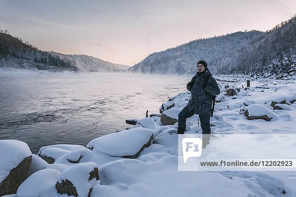 Russland  Oblast Amur  Mann am Flussufer von Bureya im Winter