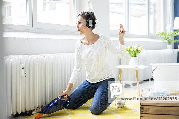 Frau zu Hause mit Kopfhörern  die den Boden saugen.