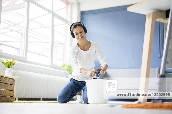 Lächelnde Frau zu Hause mit Kopfhörern  die den Boden abwischen.