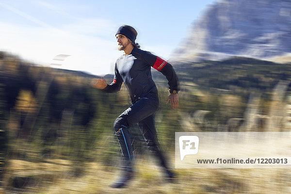 Mann läuft schnell auf dem Bergweg