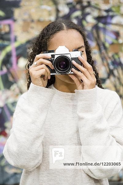 Deutschland  Berlin  junge Frau beim Fotografieren mit einer alten Kamera vor Graffiti