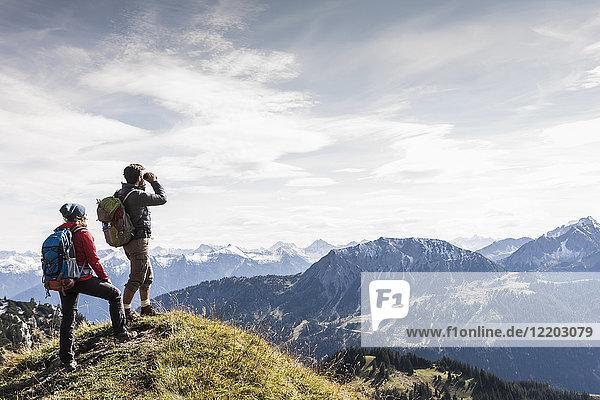 Österreich  Tirol  junges Paar in der Bergwelt stehend mit Blick auf die Landschaft