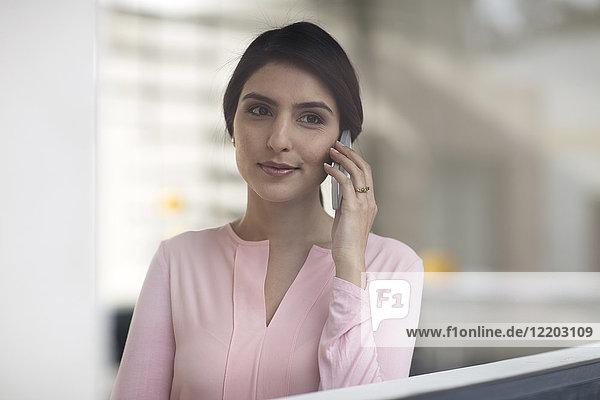 Porträt einer jungen Frau am Handy im Büro