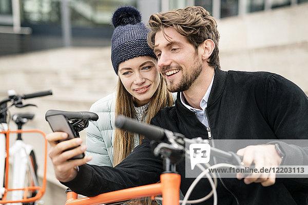 Lächelndes Paar mit Fahrrädern und Handy in der Stadt