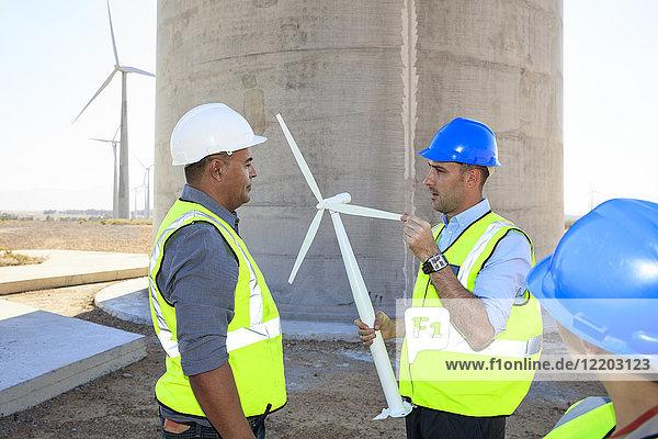 Drei Ingenieure mit Windkraftanlagenmodell diskutieren über einen Windpark