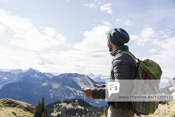 Österreich  Tirol  junger Mann mit Karte in Berglandschaft