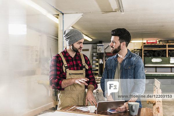 Zwei Männer mit Tablette diskutieren im Workshop