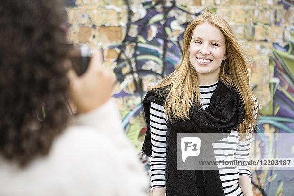 Deutschland  Berlin  junge Frau fotografiert ihren Freund s vor Graffiti