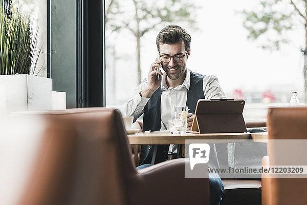 Lächelnder junger Mann  der in einem Café arbeitet und am Handy redet.