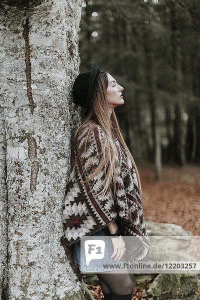 Junge Frau mit Hut und Poncho an Baumstamm lehnend im Herbstwald