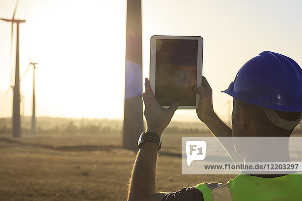 Engineer taking picture with a tablet of a wind farm at sunset