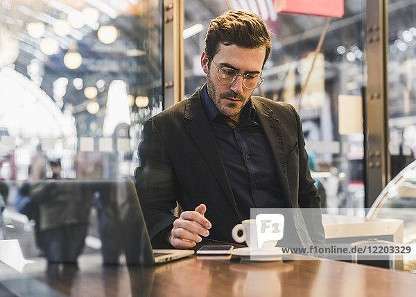 Jungunternehmer in einem Café am Bahnhof mit Kaffee  Laptop und Handy