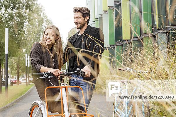 Lächelndes Paar mit Fahrrädern auf der Straße