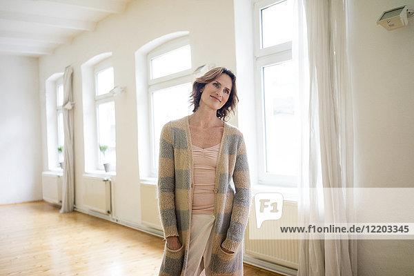 Porträt einer lächelnden reifen Frau  die in einem leeren Raum steht.