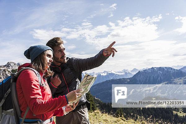 Österreich  Tirol  junges Paar mit Karte in der Bergwelt unterwegs