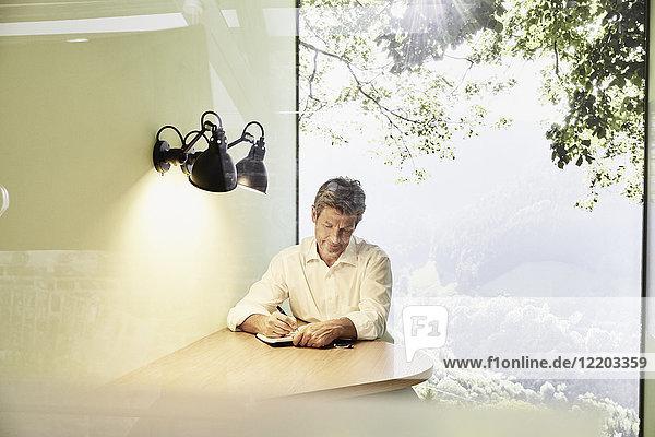 Geschäftsmann beim Schreiben in Buch am Tisch im modernen Büro mit Panoramafenster