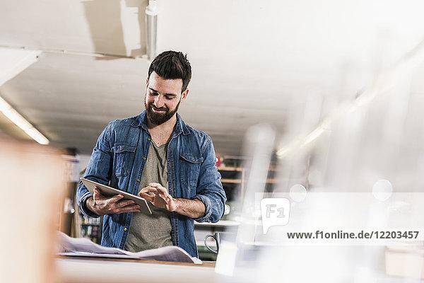 Lächelnder Mann mit Tablette und Entwurf in der Werkstatt