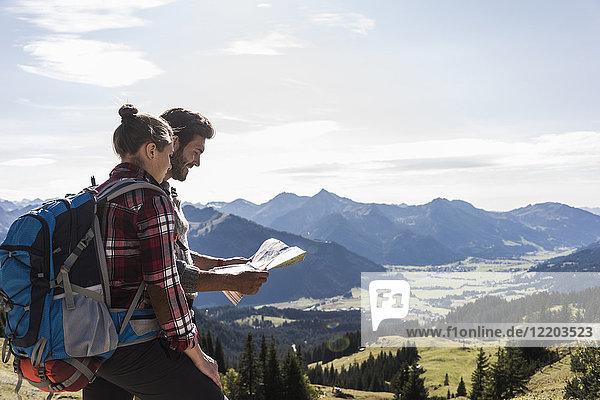 Österreich  Tirol  junges Paar auf der Karte in der Berglandschaft