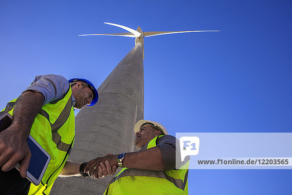 Low angle view of technicians shaking hands in front of wind turbine
