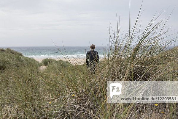 UK  Cornwall  Hayle  businessman standing in beach dunes looking at view