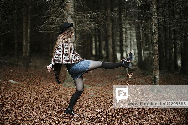 Junge Frau spielt mit Blättern im Herbstwald
