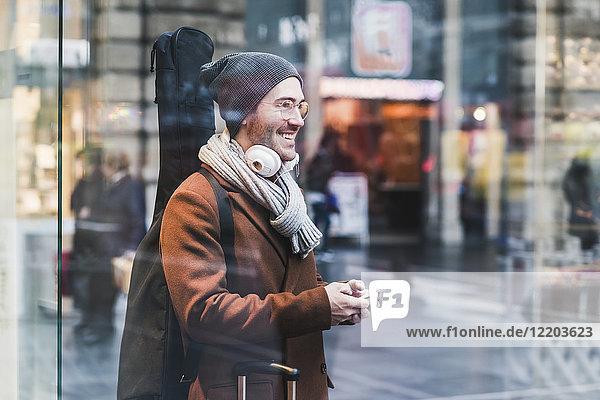 Lächelnder junger Mann mit Gitarrenkoffer und Handy