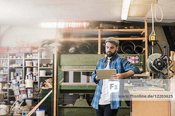 Mann mit Tablette in der Werkstatt