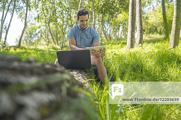Man with laptop sitting on tree trunk in nature using tablet