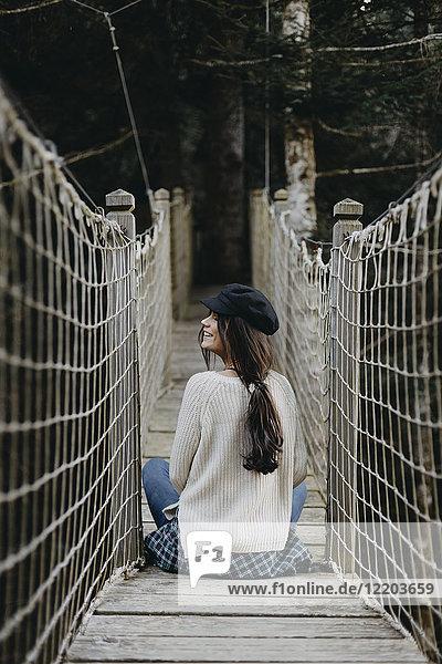 Lächelnde junge Frau auf einer Hängebrücke sitzend