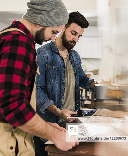 Zwei Männer mit Tablette beim Betrachten des Entwurfs in der Werkstatt